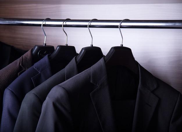 Męskie kurtki garniturowe wiszące w szafie
