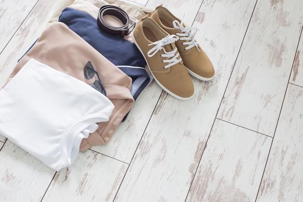 Męskie letnie podstawowe ubrania i buty na starej drewnianej podłodze