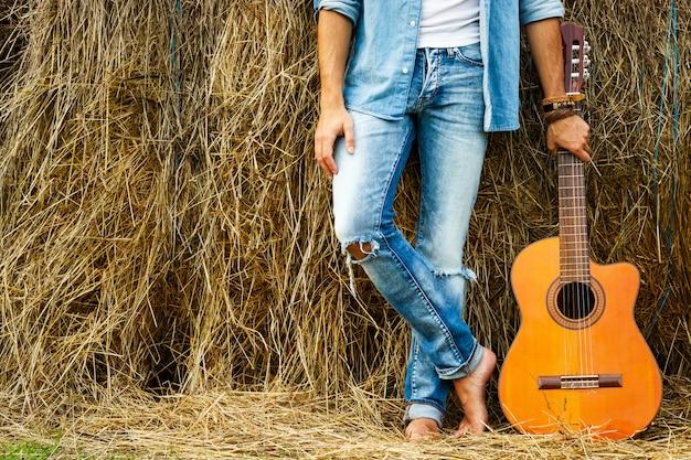 Męskie nogi i gitara akustyczna