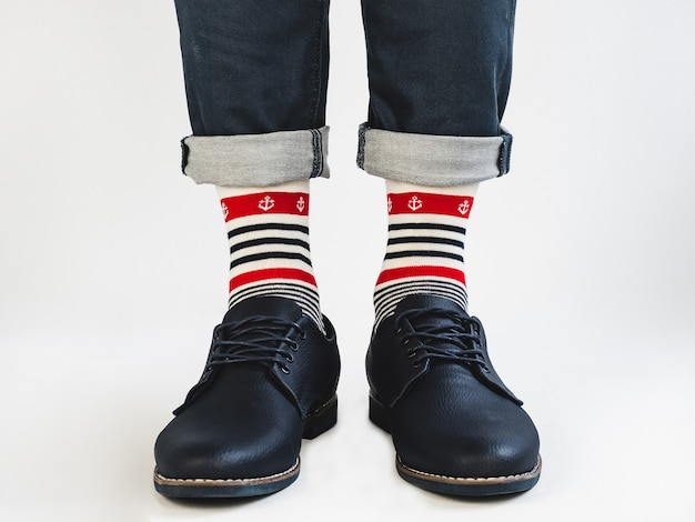 Męskie nogi, jasne skarpetki w paski i buty