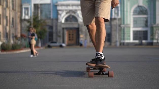 Męskie nogi jasnoskórego sportowca na longboardzie pewnie poruszają się do przodu