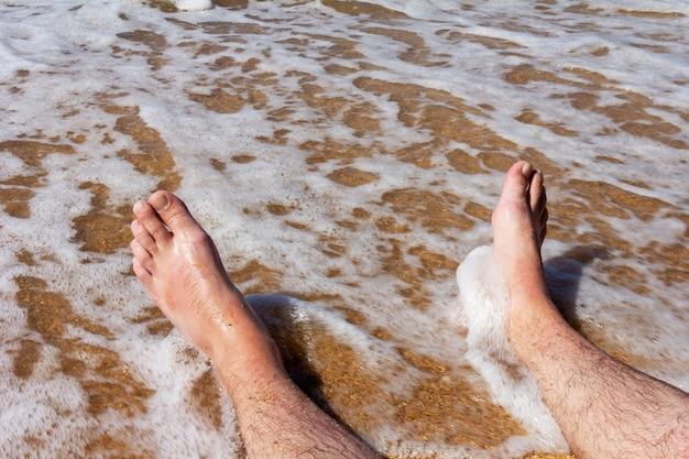 Męskie nogi na piaszczystej plaży w morskich falach