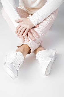Męskie nogi w białych trampkach