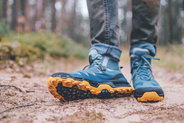 Męskie nogi w butach trekkingowych do aktywności na świeżym powietrzu na leśnej drodze