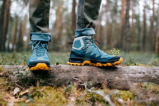 Męskie nogi w butach trekkingowych do aktywności na świeżym powietrzu, stojąc na powalonym drzewie.