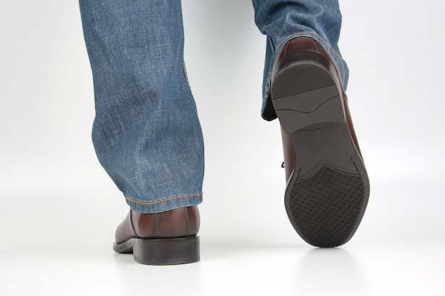 Męskie nogi w dżinsach i brązowe klasyczne buty na białej przestrzeni