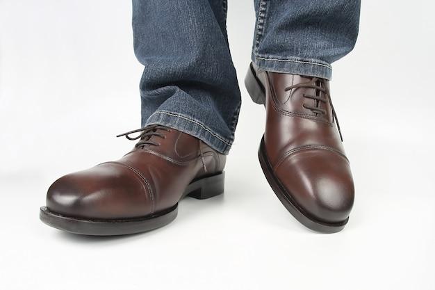 Męskie nogi w dżinsach i brązowe klasyczne buty na białej ścianie