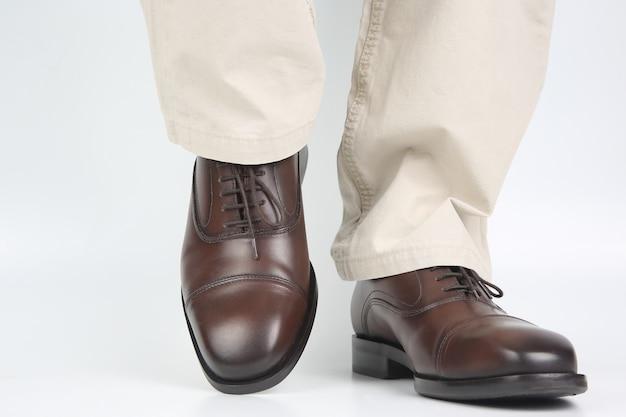 Męskie nogi w dżinsach i brązowych klasycznych butach na białej powierzchni