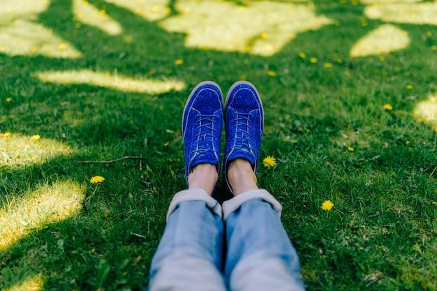 Męskie nogi w dżinsach i butach odizolowywających na trawy tle