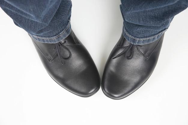 Męskie nogi w dżinsach i czarne klasyczne buty na białym tle