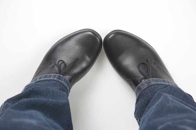 Męskie nogi w dżinsach i czarnych klasycznych butach na białym tle