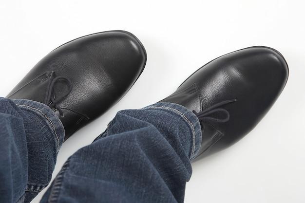 Męskie nogi w dżinsach i czarnych klasycznych butach