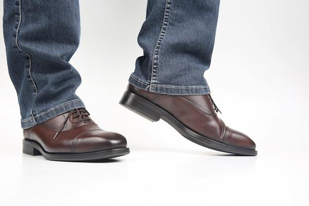 Męskie nogi w dżinsach okute w klasyczne brązowe buty typu oxford