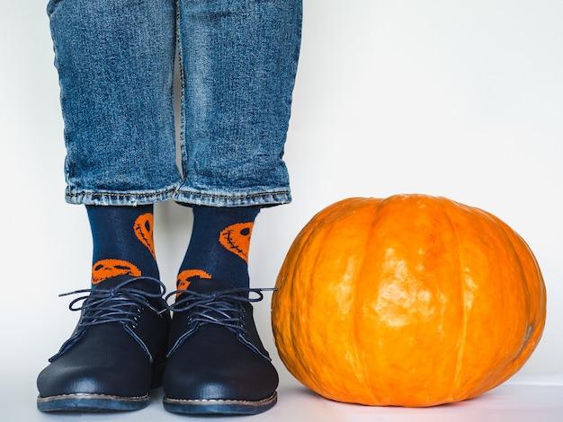 Męskie nogi w modnych butach i jasnych skarpetkach obok dyni
