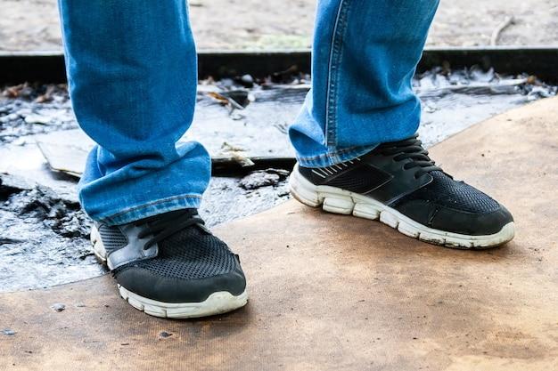Męskie nogi w niebieskich dżinsach i czarnych tenisówkach z białymi podeszwami stoją na brudnej, olejowanej desce ze sklejki. brudne miejsce pracy mistrza samochodu