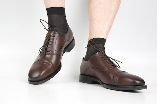 Męskie nogi w skarpetkach i brązowe buty na białym tle