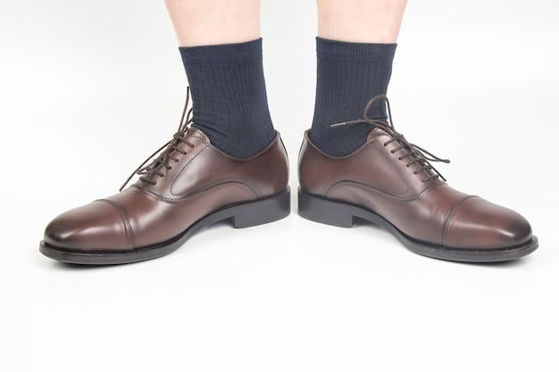 Męskie nogi w skarpetkach i brązowe klasyczne buty na białym tle