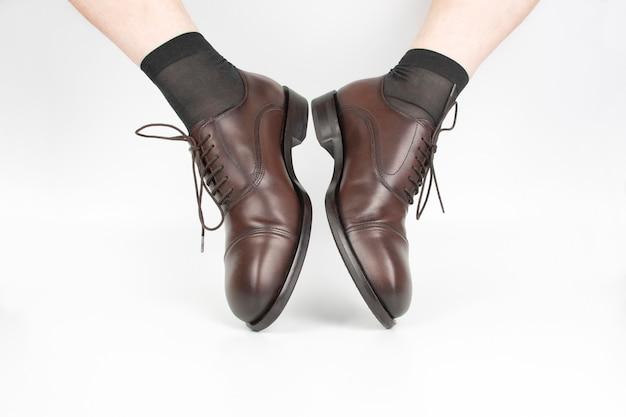 Męskie nogi w skarpetkach i brązowe klasyczne buty na białym