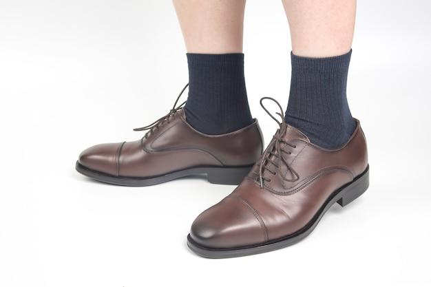 Męskie nogi w skarpetkach i brązowych klasycznych butach