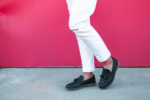 Męskie nogi w skórzanych czarnych butach i białych spodniach przy jasnoróżowej ścianie