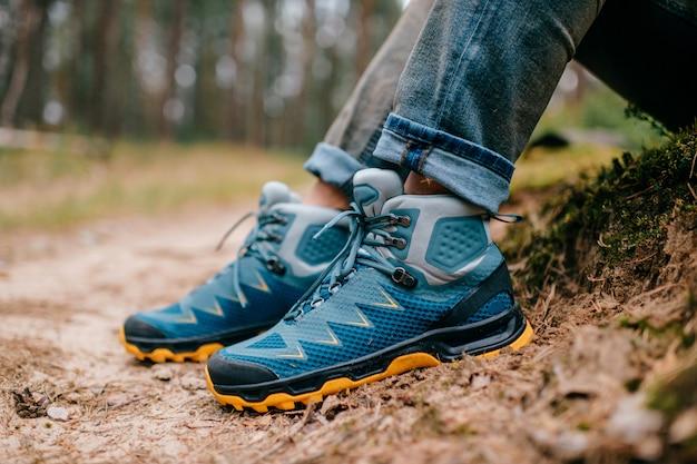 Męskie nogi w sportowych butach turystycznych. męskie nogi w butach trekkingowych do aktywności na świeżym powietrzu