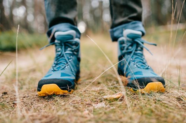 Męskie nogi w sportowych butach turystycznych.