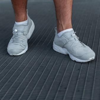Męskie nogi w sportowych modnych białych trampkach. stylowy, swobodny wygląd. szczegóły codziennego wyglądu. modne trampki męskie. moda uliczna. zbliżenie.