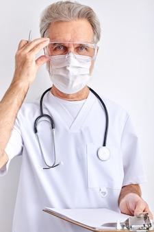 Męskie okulary korekcyjne lekarza, w masce ochronnej na twarz dla ochrony przed chorobą wirusową, pozowanie