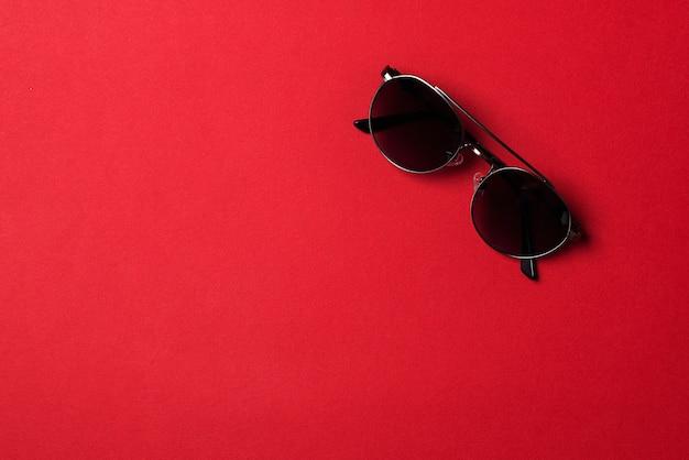 Męskie okulary przeciwsłoneczne na czerwonym tle papieru. koncepcja moda okulary męskie. minimalistyczny styl, płaski układ.