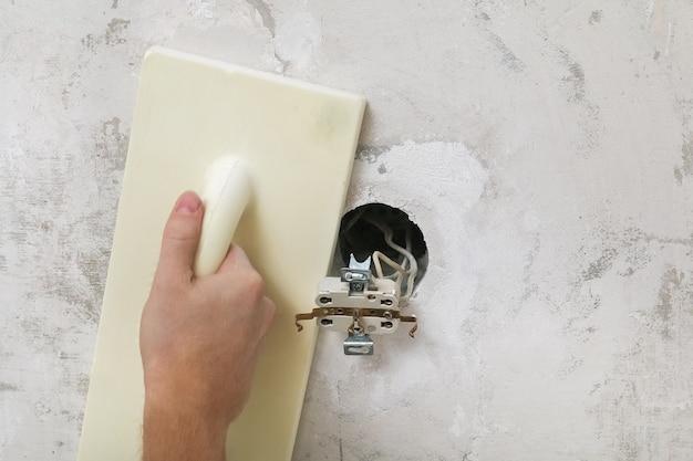 Męskie pasty robocze szlifują ścianę