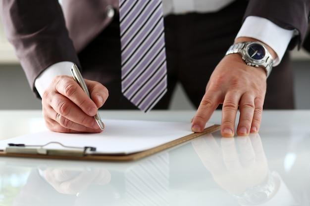 Męskie ramię w formie wypełnienia garnituru i krawata przypięte do podkładki ze srebrnym długopisem zbliżenie. szyldowy gest czytający paktu sprzedaży agenta bankowego praca robi notatce pożyczka kredyt hipoteczny inwestycja finanse naczelny prawo wykonawcze
