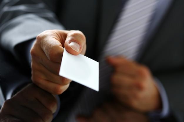 Męskie ramię w garniturze daje gościowi pustą wizytówkę