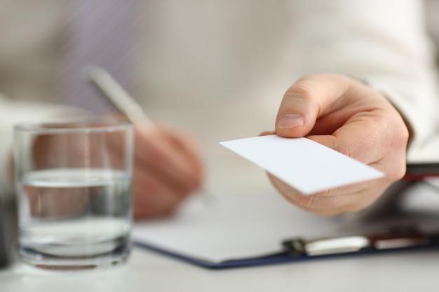 Męskie ramię w kolorze daje odwiedzającemu pustą kartę telefoniczną