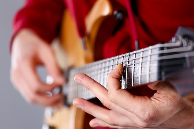 Męskie ramiona grające na gitarze elektrycznej o klasycznym kształcie