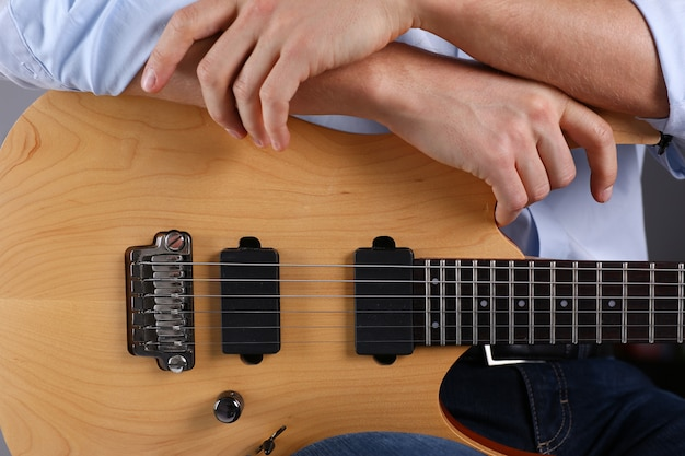 Męskie ramiona grające na gitarze elektrycznej w klasycznym kształcie