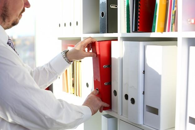 Męskie ramiona wybierają czerwony folder plików z biurowej półki z książkami