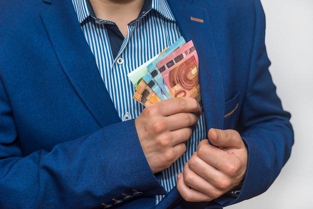 Męskie ręce chowają banknoty do kieszeni