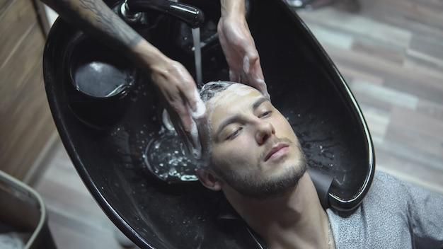 Męskie ręce fryzjera z tatuażem myją głowę klienta - młody człowiek w umywalce u fryzjera