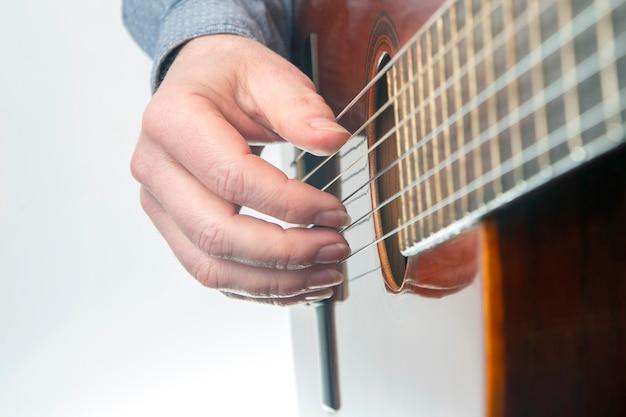 Męskie ręce gitarzysty z gwoździami podczas grania muzyki