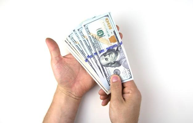 Męskie ręce liczą pieniądze dolary na białym tle