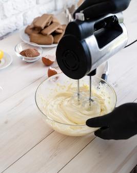 Męskie ręce mieszania ciasta z elektrycznym mikserem w kuchni zbliżenie