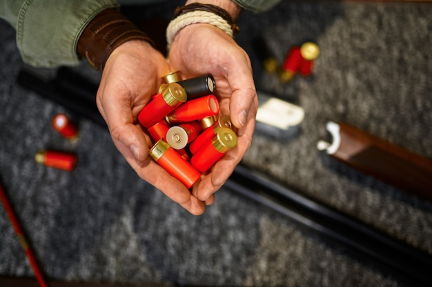 Męskie ręce myśliwego trzymają naboje w sklepie z bronią