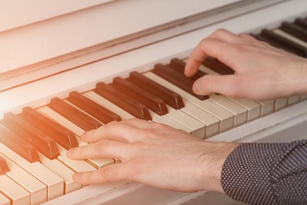 Męskie ręce na klawiaturze fortepianu ze światłem słonecznym.