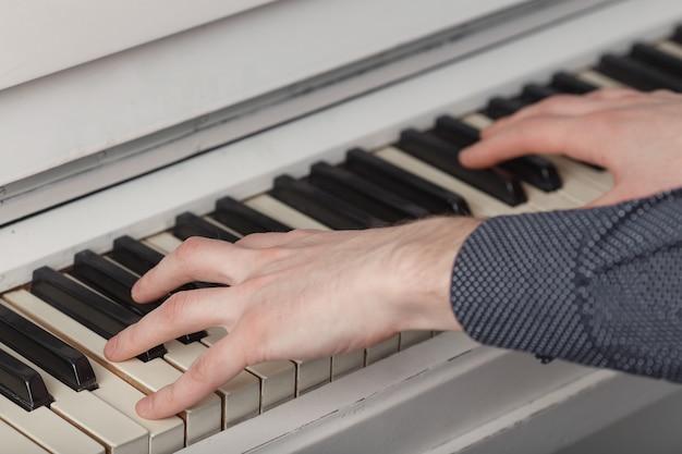 Męskie ręce na klawiaturze fortepianu.