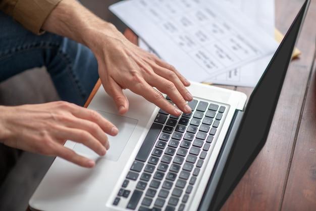 Męskie ręce nad pisaniem na klawiaturze laptopa