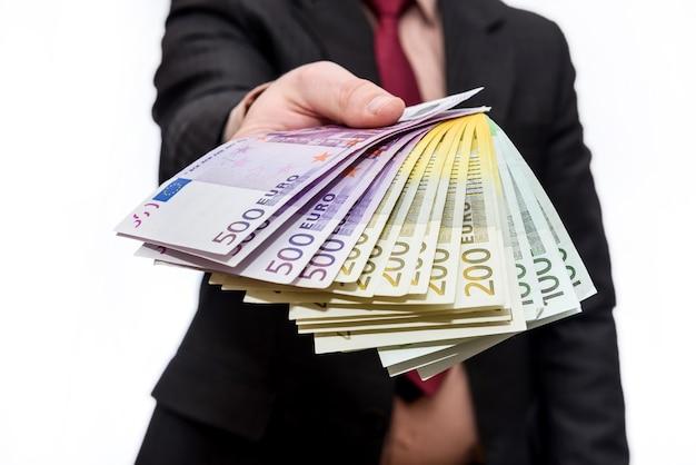 Męskie ręce oferujące banknoty euro w wentylatorze