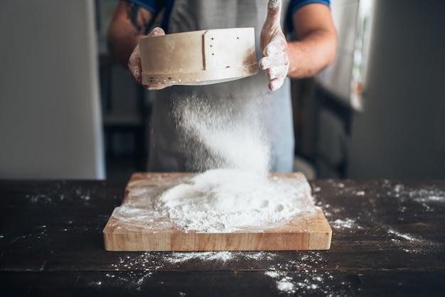 Męskie ręce piekarza filtrują mąkę przez sito nad deską do krojenia. przygotowanie chleba. domowa piekarnia