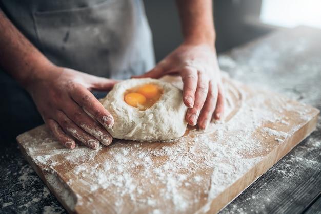 Męskie ręce piekarza mieszają ciasto z jajkiem. przygotowanie chleba. domowa piekarnia
