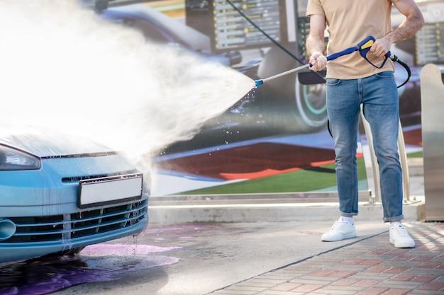 Męskie ręce podlewają samochód wodą z węża