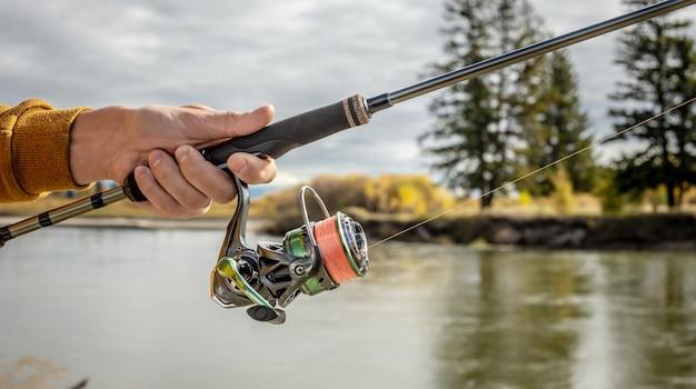 Męskie ręce rybaka trzymają zbliżenie przędzenia. koncepcja połowów w jesiennym lesie